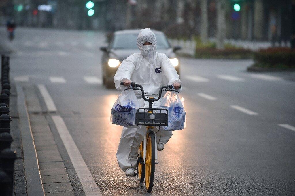 Un habitant portant une combinaison de protection fait du vélo dans l'épicentre du virus à Wuhan, dans la province centrale de Hubei, en Chine